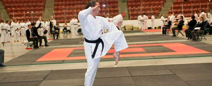 man in karate uniform performing karate kick in go auto arena at Servus Place